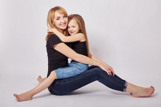 Mãe e filha se abraçando, sentada no chão. família amorosa. rússia, sverdlovsk, 6 de janeiro de 2019