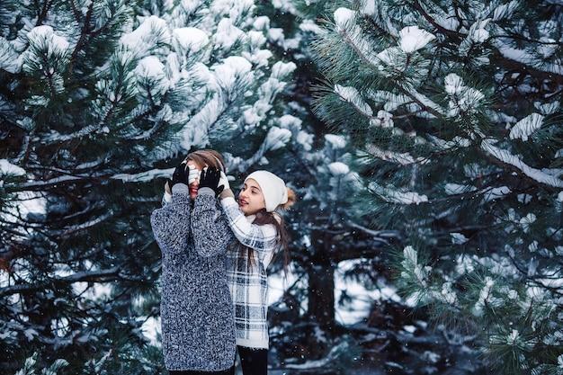 Mãe e filha se divertem brincando na floresta de inverno.
