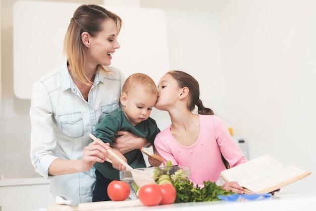 Mãe e filha se divertem enquanto prepara uma salada.