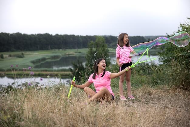 Mãe e filha se divertem juntas, fazem grandes bolhas de sabão, recreação ao ar livre.