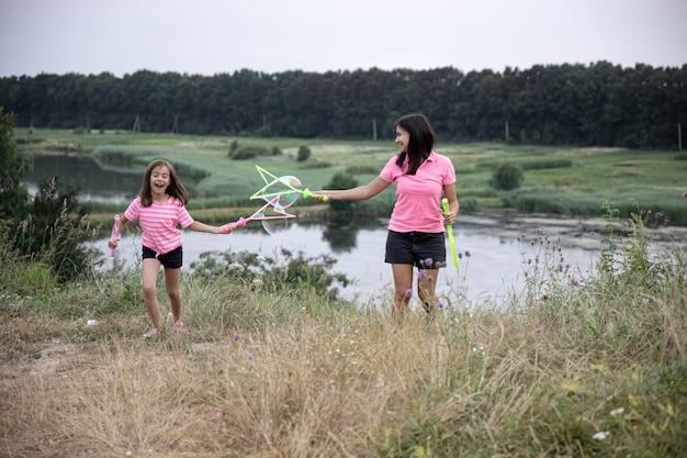 Mãe e filha se divertem juntas, fazem grandes bolhas de sabão, recreação ativa ao ar livre para a família.