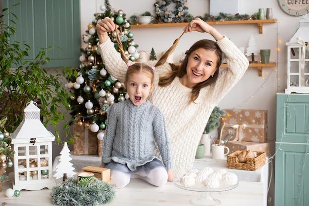 Mãe e filha se divertem na cozinha de natal em casa.