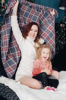 Mãe e filha se divertindo com cobertor