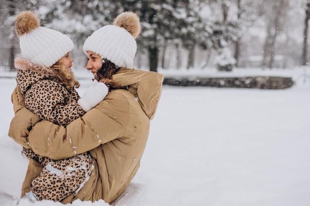 Mãe e filha se divertindo em um parque cheio de neve