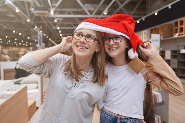 Mãe e filha se divertindo, fazendo compras juntas para o natal, usando chapéu de papai noel