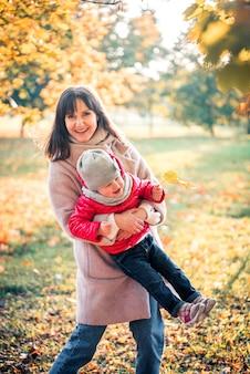 Mãe e filha se divertindo no parque outono entre as folhas que caem. estilo de vida ativo