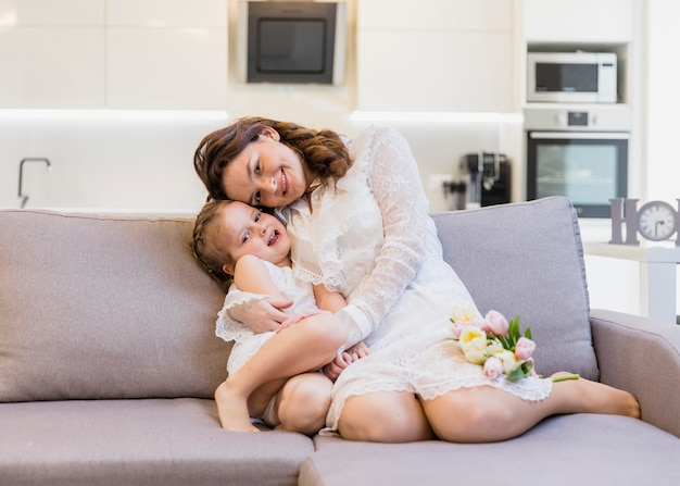 Mãe e filha se divertindo no sofá em casa