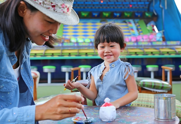 Mãe e filha se divertindo para pintar na boneca de estuque
