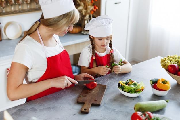 Mãe e filha se divertir na cozinha cozinhar legumes diferentes para um jantar
