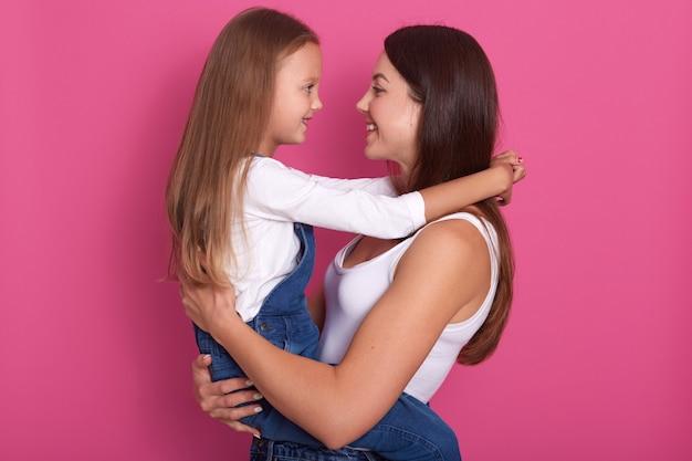 Mãe e filha se olham, mamãe segurando seu filho encantador