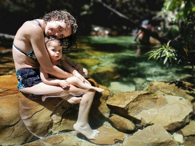 Mãe e filha se refrescar no verão na cachoeira.