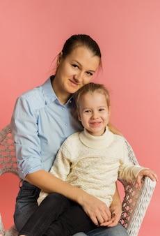 Mãe e filha se sentam em uma cadeira e se abraçam em um fundo rosa