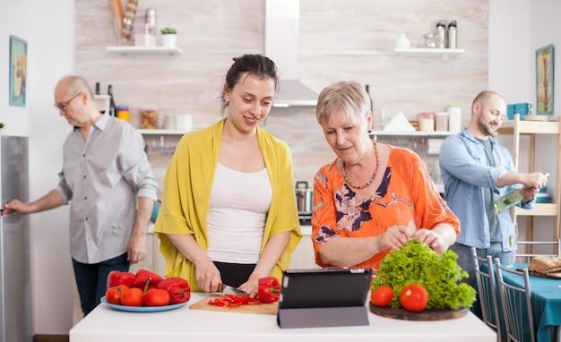 Mãe e filha seguindo a receita online do tablet para salada de legumes, corte de pimentão e alface. abertura de marido