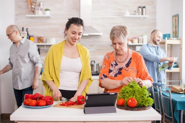 Mãe e filha seguindo a receita online do tablet para salada saudável. marido, sorrindo, segurando uma garrafa de vinho. último homem abrindo a porta da geladeira na cozinha.