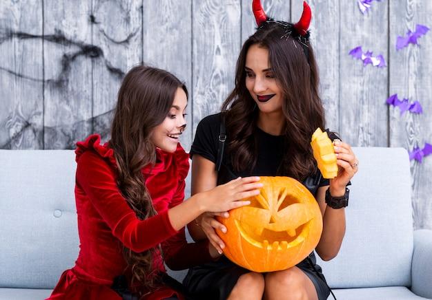 Mãe e filha segurando abóbora esculpida para o halloween