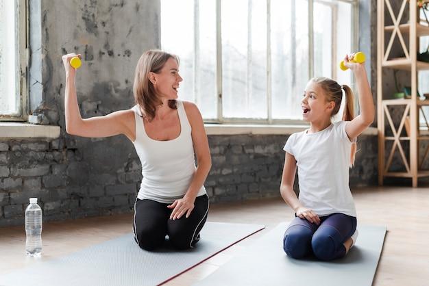 Mãe e filha segurando pesos em tapetes de ioga
