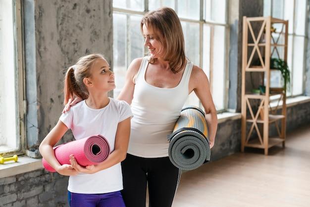 Mãe e filha segurando tapetes de ioga