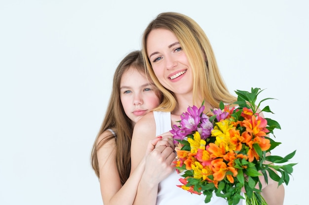 Mãe e filha segurando um arranjo floral festivo. composição de alstroemeria colorida