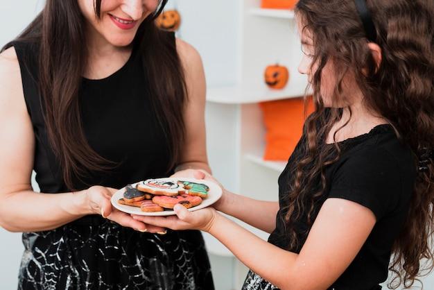 Mãe e filha segurando um prato com biscoitos