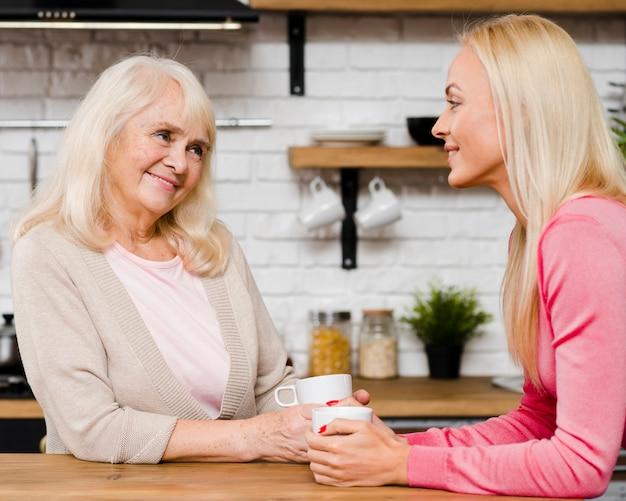 Mãe e filha segurando xícaras de café e conversando