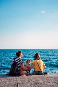 Mãe e filha sentada à beira-mar com cachorro