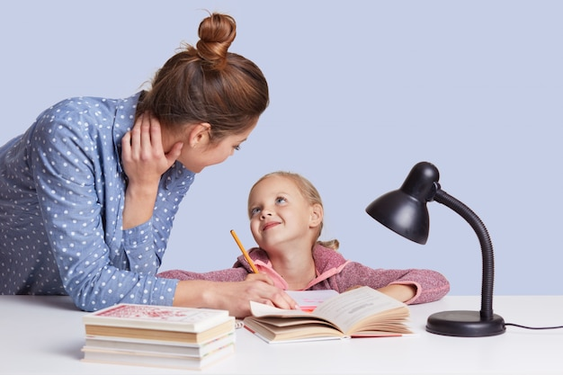 Mãe e filha sentada à mesa, rodeada de livros, olhando um ao outro com amor, fazendo dever de casa juntos, múmia ajuda a menina a fazer somas. crianças, escola, conceito de educação.