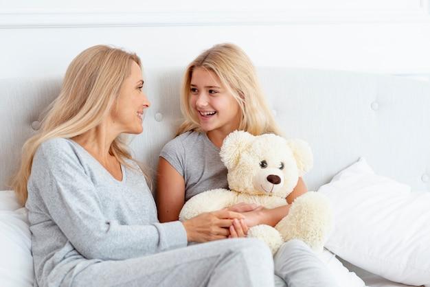 Mãe e filha sentada de pijama