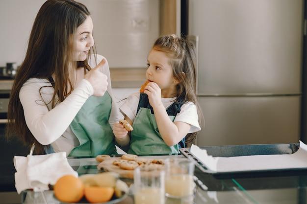 Mãe e filha sentada em uma cozinha com biscoitos
