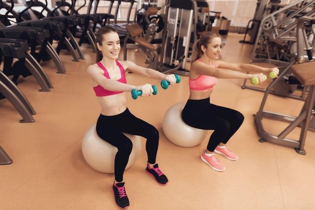 Mãe e filha sentada fazendo exercícios com halteres.
