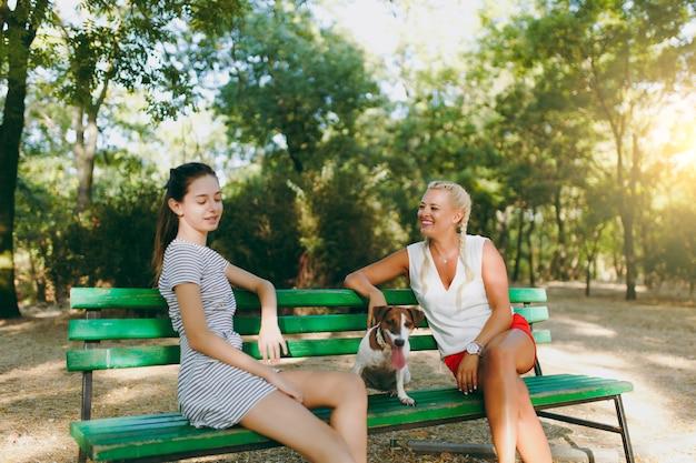 Mãe e filha sentada no banco com um pequeno cachorro engraçado. pequeno animal de estimação jack russel terrier brincando ao ar livre no parque. cachorro e mulheres. família descansando ao ar livre.