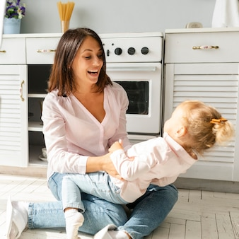 Mãe e filha sentada no chão da cozinha