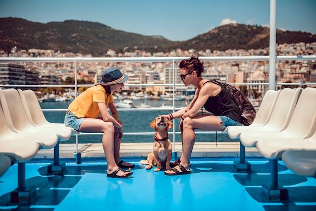 Mãe e filha sentada no convés de uma balsa com um cachorro