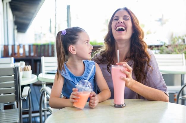 Mãe e filha sentadas ao lado do café