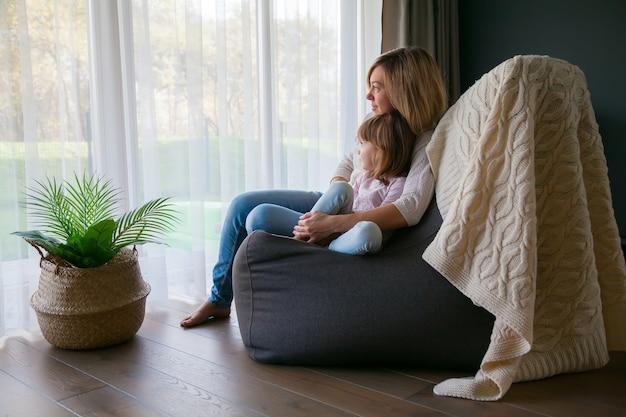 Mãe e filha sentadas confortavelmente em uma cadeira de pufe, se abraçando e olhando pela janela