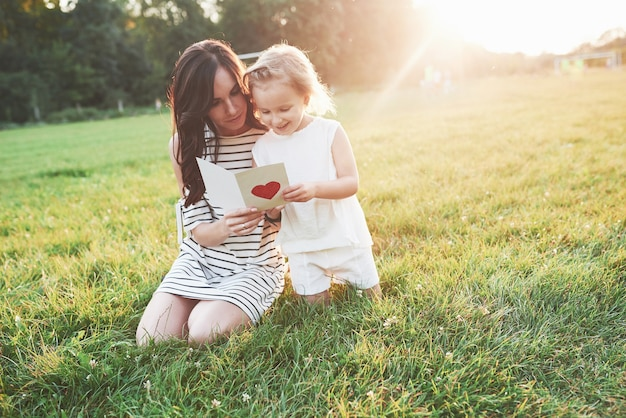 Mãe e filha sentadas e lendo o livrinho com o coração na capa