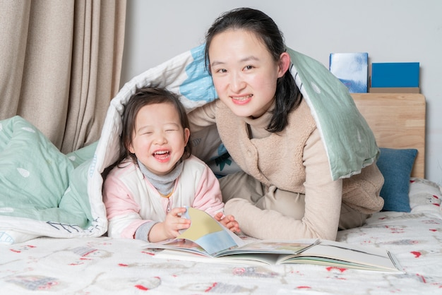 Mãe e filha sentadas na cama lendo juntas