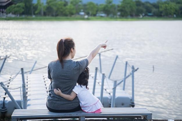 Mãe e filha sentadas olhando para o rio