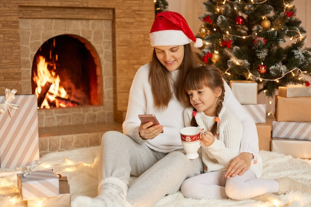 Mãe e filha sentadas perto da árvore de natal, se abraçando, se comunicando por videochamada, se divertindo.