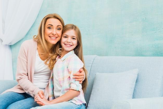 Mãe e filha sentados juntos e abraçando