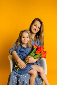 Mãe e filha sentam-se em uma cadeira com um buquê de tulipas vermelhas e olham para a frente em uma parede amarela