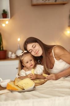 Mãe e filha sentam-se na cozinha e comem um pedaço de queijo.