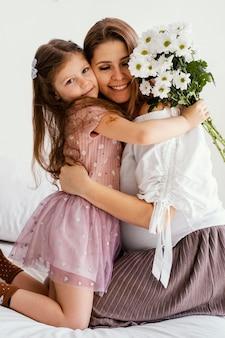Mãe e filha sorridente com buquê de flores da primavera