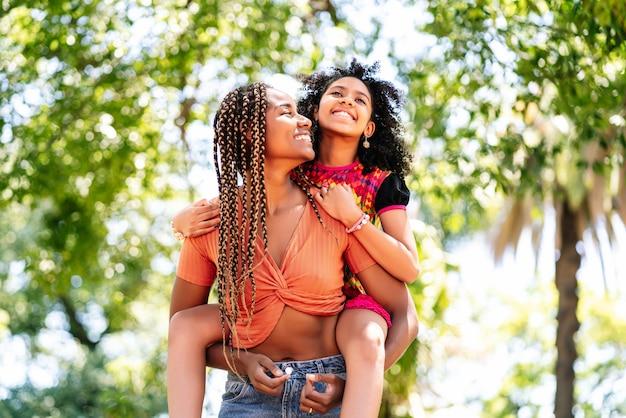Mãe e filha sorrindo e curtindo um dia juntas no parque