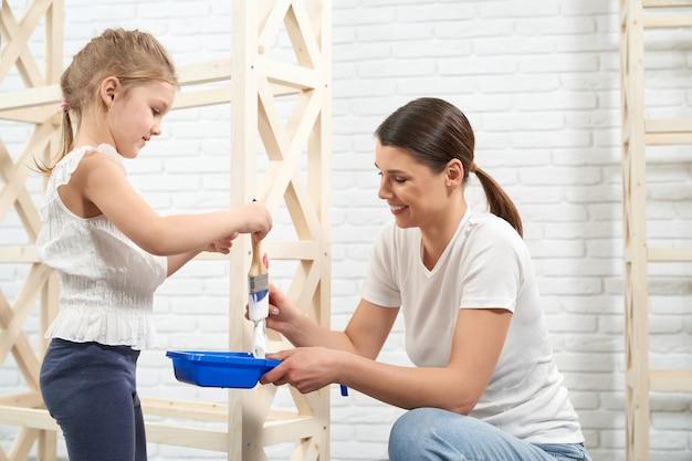 Mãe e filha sorrindo e pintando um rack de madeira