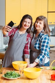 Mãe e filha sorrindo e posando na cozinha
