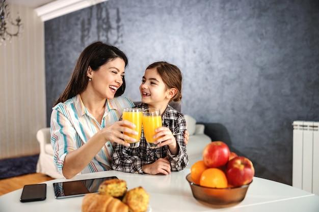 Mãe e filha sorrindo, sentadas à mesa de jantar e tomando um café da manhã saudável