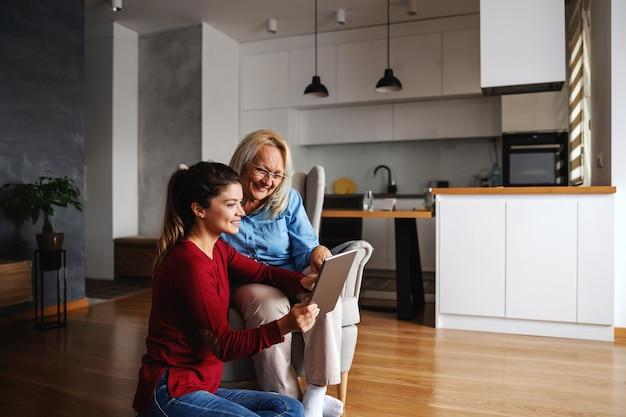 Mãe e filha sorrindo, sentadas em casa juntas e apontando para o tablet