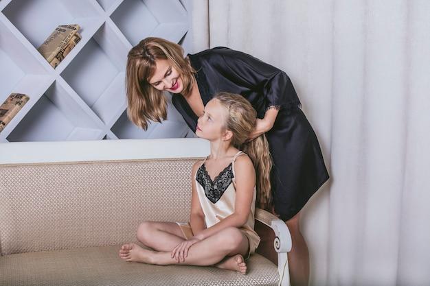 Mãe e filha sozinhas em casa lindas, elegantes e divertidas. família amorosa feliz juntos para passar um tempo relaxante.