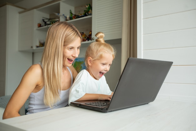 Mãe e filha surpresas sentadas no laptop em casa