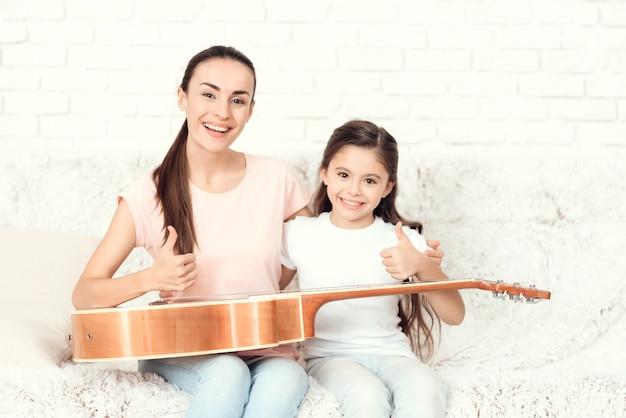 Mãe e filha têm uma guitarra no colo.